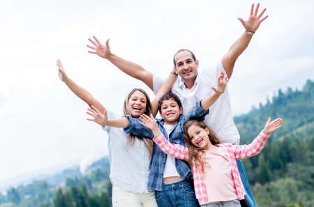 family celebration: Happy family with arms up outdoors celebrating
