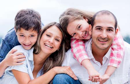 sonrisa: Retrato de una familia feliz y amorosa sonriendo al aire libre Foto de archivo