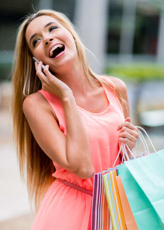 Happy female shopper talking on the phone and smiling photo