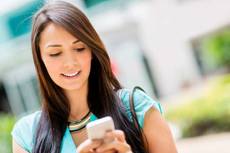cell phone: Beautiful casual woman texting on her cell phone Stock Photo