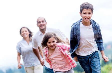 familias felices: Familia feliz divertirse correr en el parque