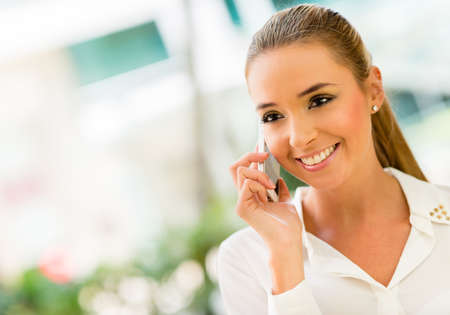 business woman phone: Business woman talking on the phone at the office