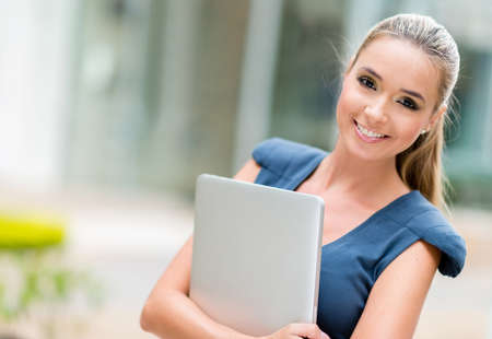 Happy business woman holding laptop and smiling photo
