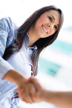 pacto: Mujer de negocios dando un apret�n de manos y una sonrisa