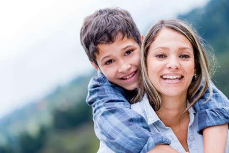 mama e hijo: Retrato de una madre feliz y su hijo sonriendo al aire libre Foto de archivo