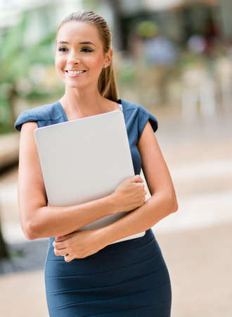 Business woman walking outdoors holding a laptop photo