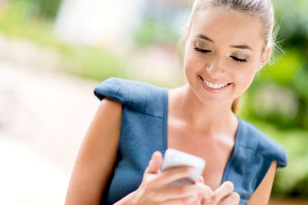 sms message: Portrait of a happy business woman texting on her phone Stock Photo