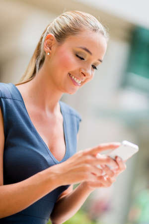 Business woman using cell phone to send a text message photo