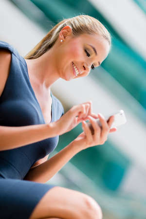 mobile: Business woman sending a text message from her mobile phone