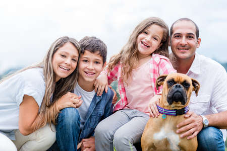 female boxer: Portrait of a happy family including the dog - outdoors Stock Photo