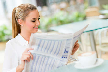 Business woman reading news in the paper at the coffee place photo