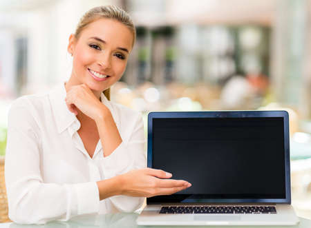 displaying: Business woman with a laptop showing something on the screen
