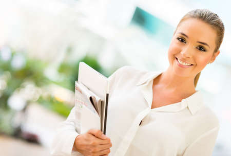 empowered: Successful business woman at the office holding documents