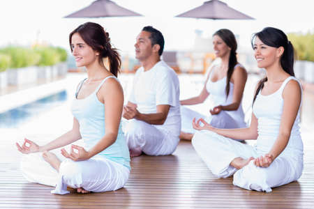 woman meditation: Group of yoga people in a class meditating