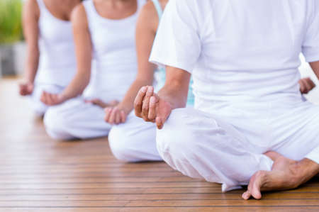 woman meditation: Group of peaceful people meditating  in a yoga studio