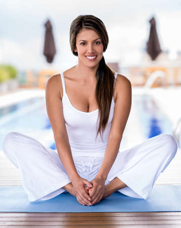 Beautiful woman practicing yoga and looking happy photo