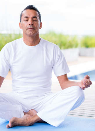 Man practicing yoga sitting with his eyes closed photo