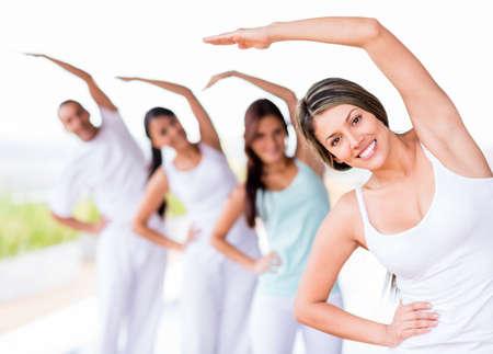 estiramientos: Grupo de personas que practican yoga y sonriente