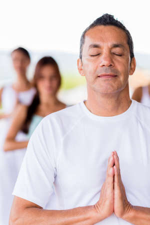 Man doing yoga with eyes closed looking very relaxed photo
