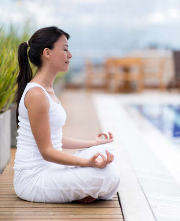 yoga: Woman meditating outdoors sitting in a yoga position Stock Photo