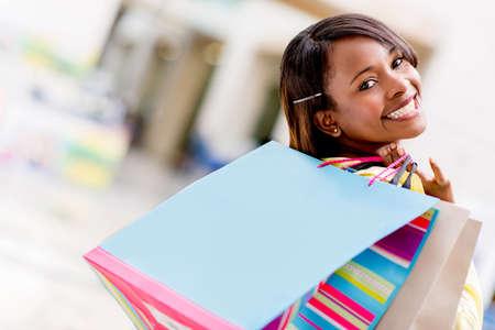 compras compulsivas: Comprador femenino feliz con bolsas de compras y sonriente Foto de archivo