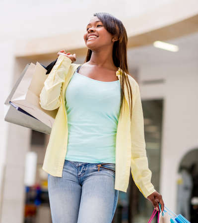 Happy woman walking at the shopping center holding bags photo