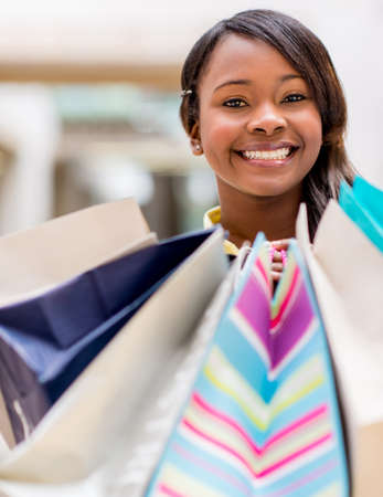 Happy female shopper holding shopping bags and smiling photo
