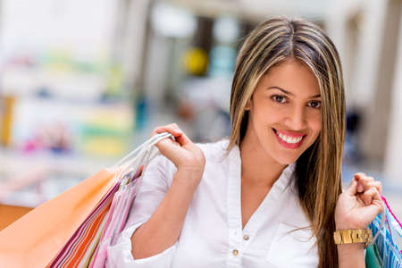 compulsive: Beautiful shopping woman holding bags and smiling