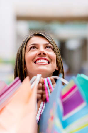 Happy female shopper looking up and holding bags photo