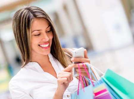 compras compulsivas: Mujer feliz con teléfono celular en un centro comercial