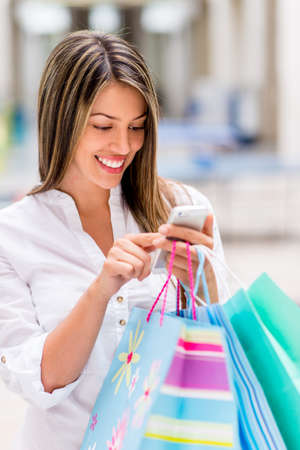 compulsive: Shopping woman using smart phone at the mall Stock Photo