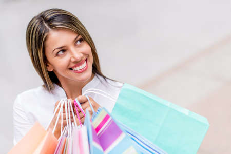 Thoughtful shopping woman looking up holding bags photo