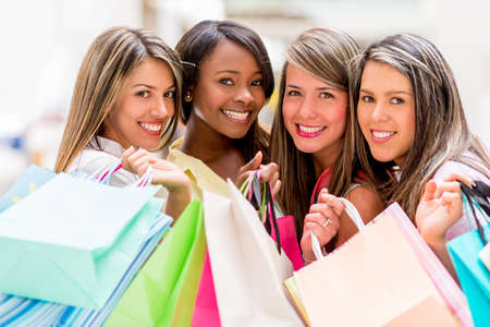 Group of shopping women holding bags ant looking happy photo