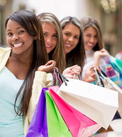 compras compulsivas: Mujeres de las compras en una fila en el centro comercial con bolsas de