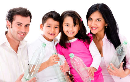 Happy family recycling plastic bottles - isolated over white photo