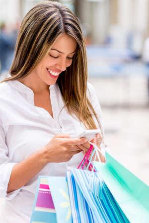 compras compulsivas: Mujer de las compras texting de su tel�fono celular Foto de archivo