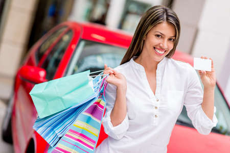 Happy woman shoppping with credit card to win a car Stock Photo - 20275329