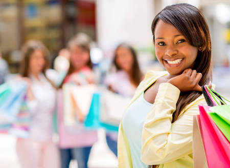 american content: Happy shopping woman smiling at the mall holding bags