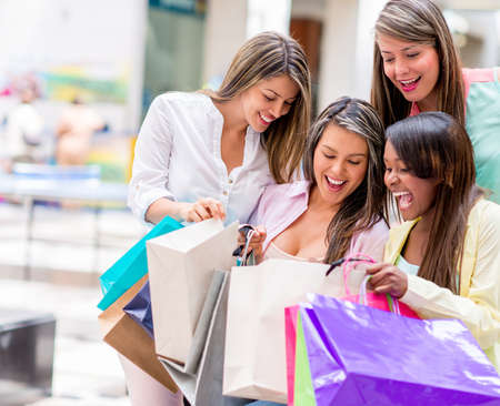 Group of happy shopping women looking in their bags photo
