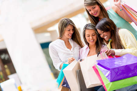 Group of shopping girls looking at their purchases photo