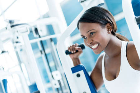Gym woman exercising on a machine and looking happy photo