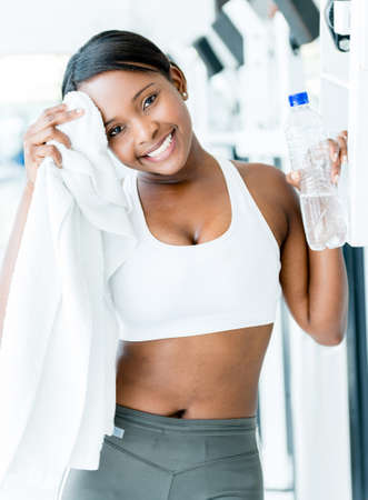 Fit woman at the gym drying her sweat with a towel photo