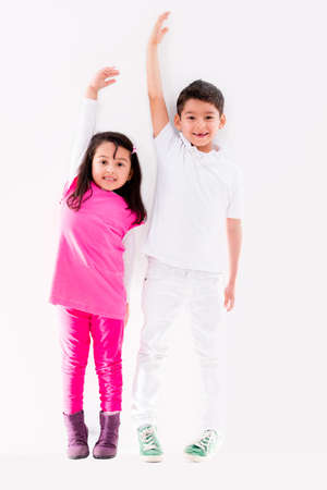 measured: Happy kids growing up to be tall leaning against the wall Stock Photo