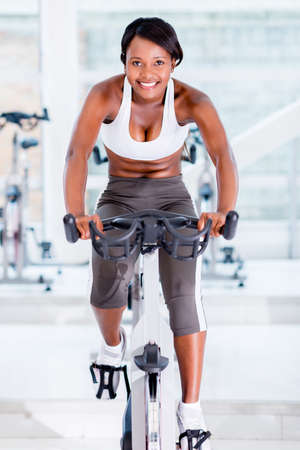 Fit woman doing spinning at the gym and smiling photo
