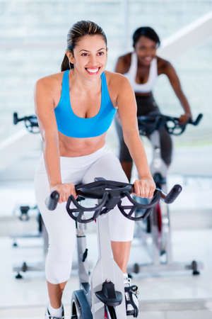 Girls doing spinning at the gym looking very happy photo