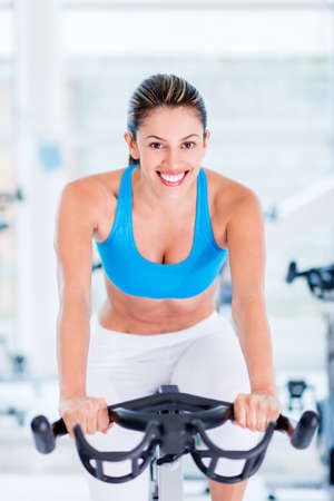 warm up exercise: Fit woman doing spinning at the gym looking very happy