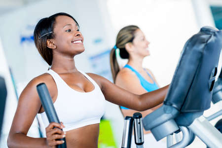 cardio fitness: Fit women exercising at the gym on an x-trainer Stock Photo