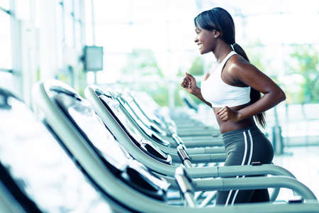 Woman running on a treadmill at the gym photo