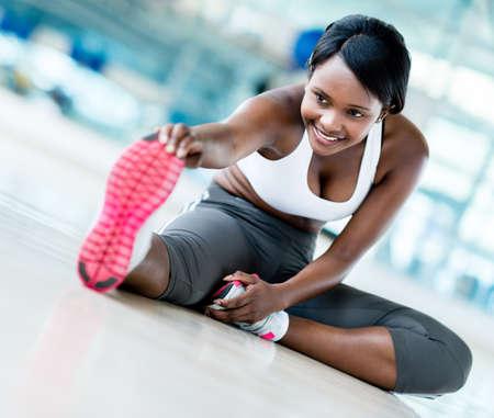 estiramientos: Mujer de la gimnasia que estira su pierna para el calentamiento
