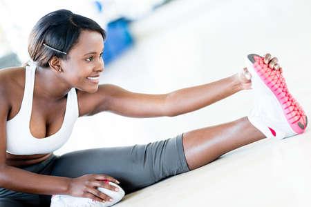 stretching: Ajustar la mujer estirando la pierna en el gimnasio Foto de archivo